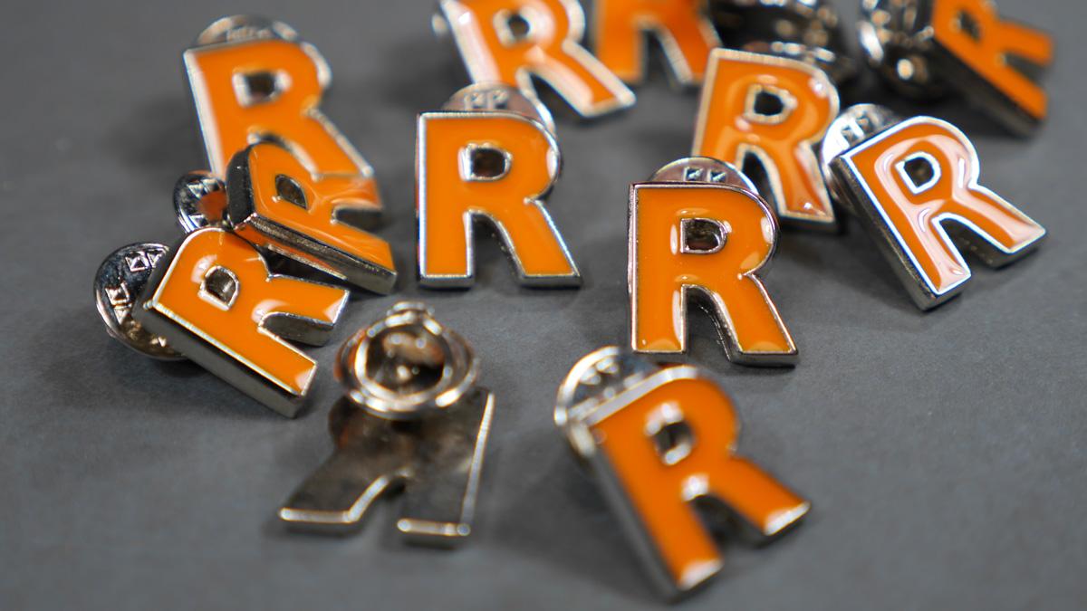 """Andarono a ruba i bellissimi pins con la """"R"""" arancione di Reggi."""